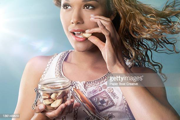 woman eating brazil nuts from a jar - brazil nut stock photos and pictures