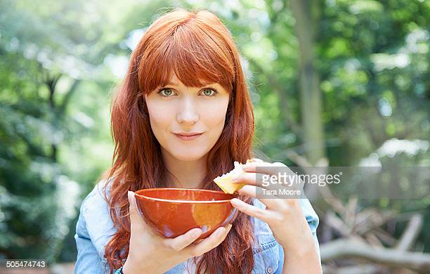 woman eating bread and soup in forest