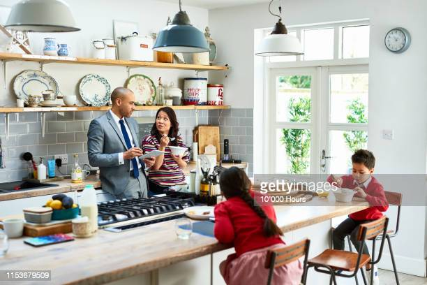 woman eating breakfast and listening to husband with digital tablet - breakfast stock pictures, royalty-free photos & images