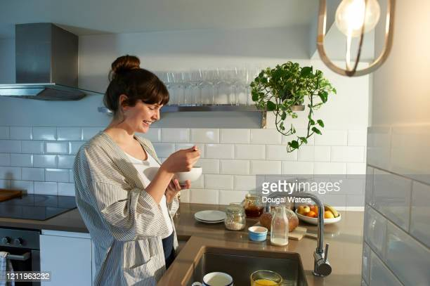 woman eating breakfast in zero waste kitchen. - breakfast stock pictures, royalty-free photos & images