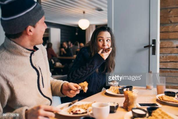 woman eating breakfast while sitting with friend at table in log cabin - temptation stock pictures, royalty-free photos & images