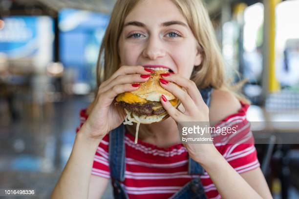 woman eating burger - cheeseburger stock pictures, royalty-free photos & images