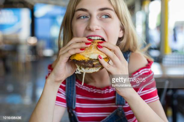 woman eating burger - obsolete stock pictures, royalty-free photos & images