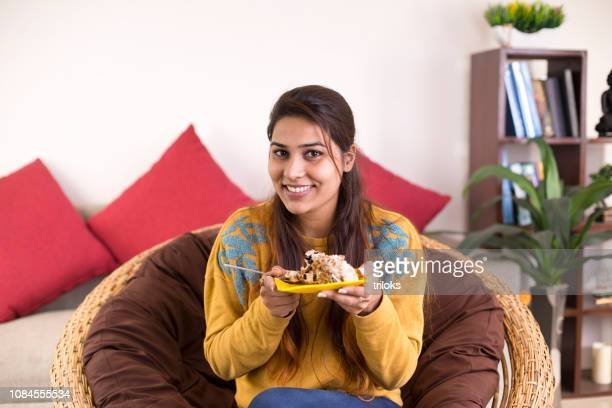 woman eating cake at home - sweet food stock pictures, royalty-free photos & images