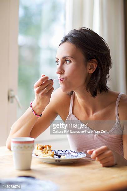 Woman eating cake at kitchen table
