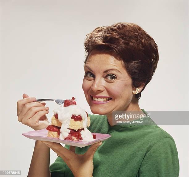 Femme, manger le gâteau, souriant, portrait