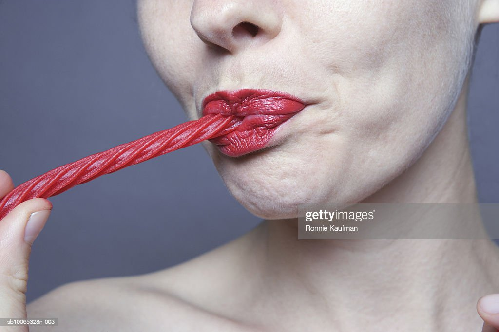 Woman eating candy cane, close-up : Foto stock
