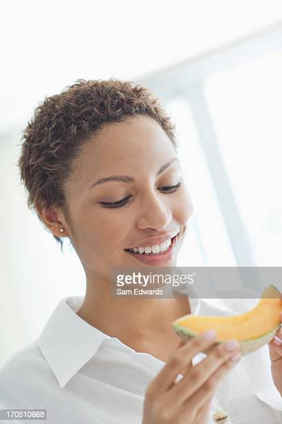 woman eating cantaloupe - muskmelon stock pictures, royalty-free photos & images