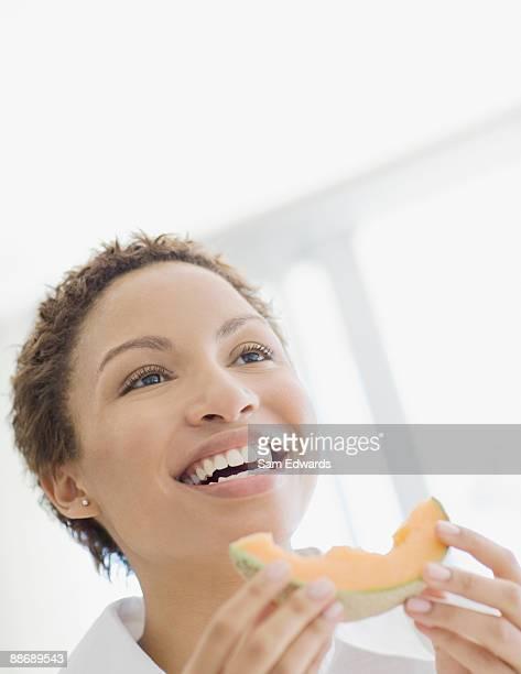 Woman eating cantaloupe