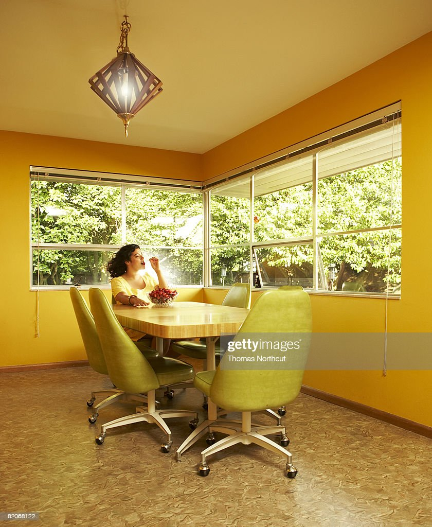 Woman eating cherries in dining room : Stock Photo
