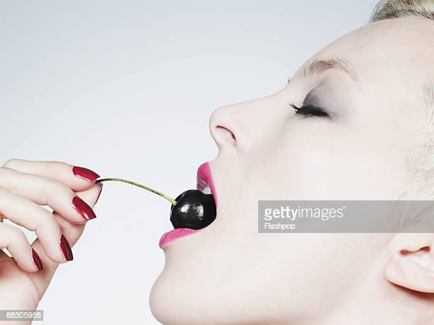 Woman eating cherry
