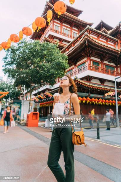 Woman eating Chinese bun    in Chinatown in Singapore