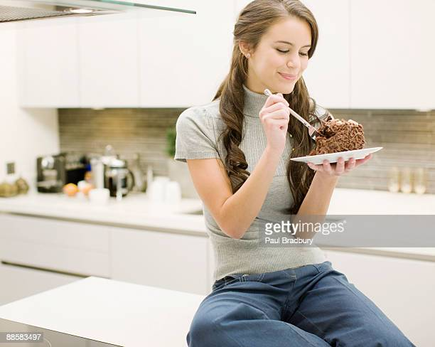 woman eating chocolate cake in kitchen - indulgence stock pictures, royalty-free photos & images
