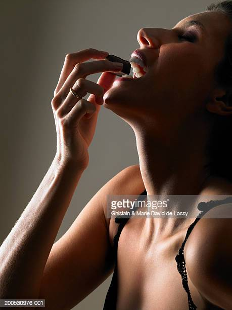 Woman eating chocolate, close-up, side view