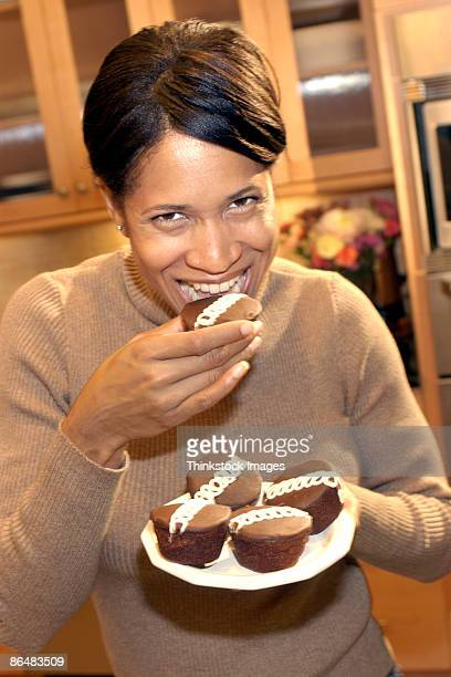 Woman eating chocolate cupcakes