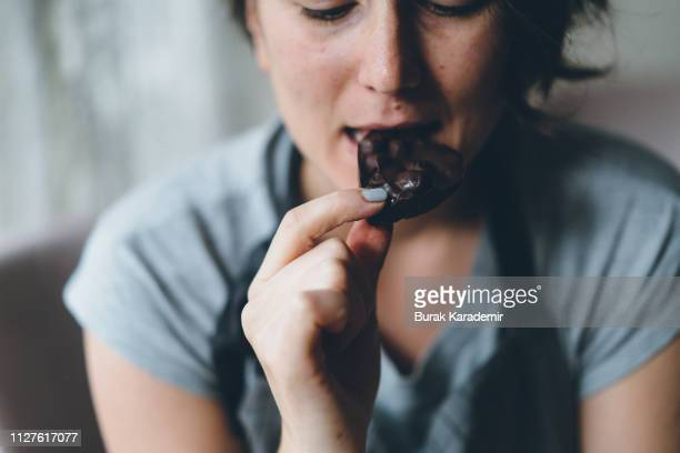 woman eating chocolate - dark chocolate stock pictures, royalty-free photos & images
