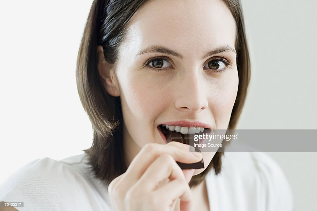 Woman eating chocolate : Stock Photo