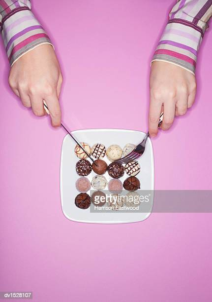 Woman Eating Chocolates from a Plate with Cutlery
