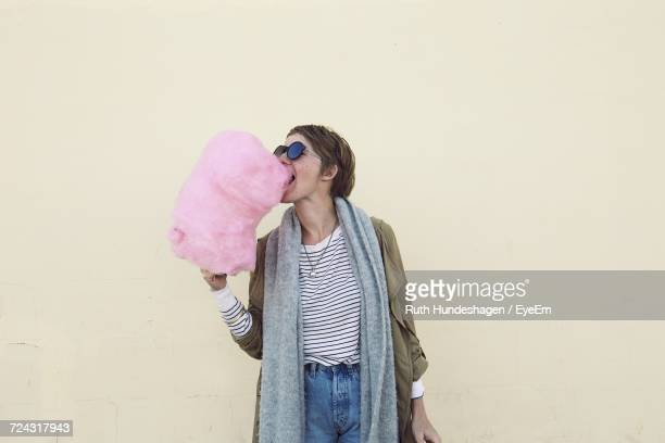 Woman Eating Cotton Candy Against Wall
