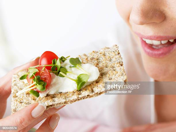 Woman eating crispbread with soft cheese, cress and tomato, close up