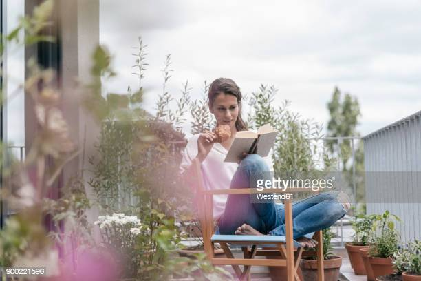 woman eating croissant and reading book on balcony - balkon stock-fotos und bilder