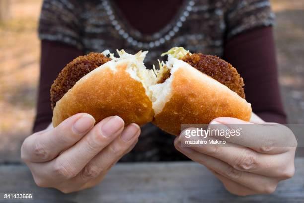 Woman Eating Croquette Sandwich