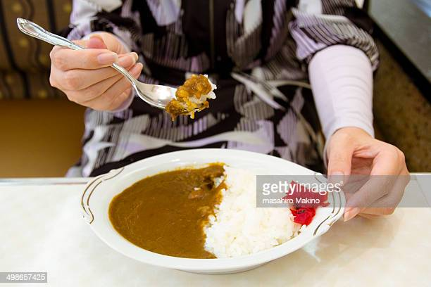 Woman eating curry and rice