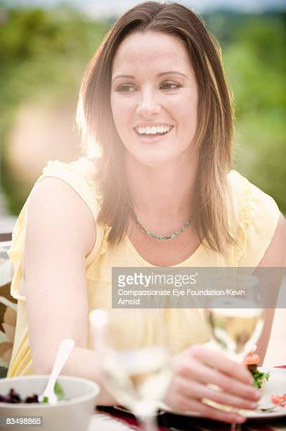 "woman eating dinner outdoors, smiling. - ""compassionate eye"" stock pictures, royalty-free photos & images"