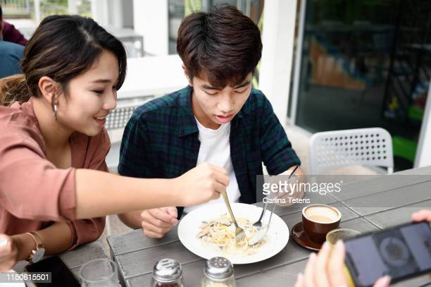 woman eating food from her brother's plate in a restaurant - steel stockfoto's en -beelden
