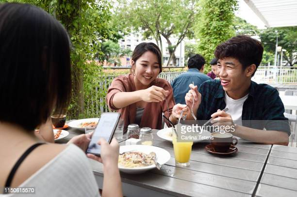 woman eating food from her brother's plate in a restaurant - outdoor dining stock pictures, royalty-free photos & images
