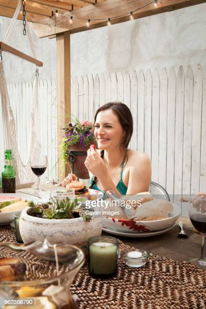 Woman eating food while sitting at table in yard