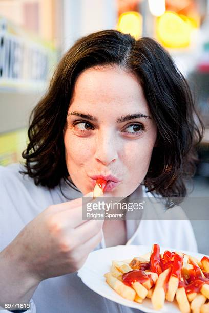 woman eating french fries - tomato sauce stock pictures, royalty-free photos & images