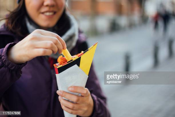 woman eating french fries potato with ketchup in brussels - belgian culture stock pictures, royalty-free photos & images