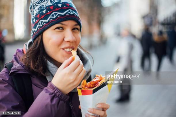 femme mangeant la pomme de terre de frites français avec le ketchup à bruxelles - région de bruxelles capitale photos et images de collection