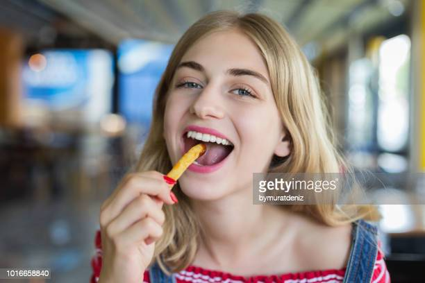 woman eating french fries potato with ketchup - fried stock pictures, royalty-free photos & images