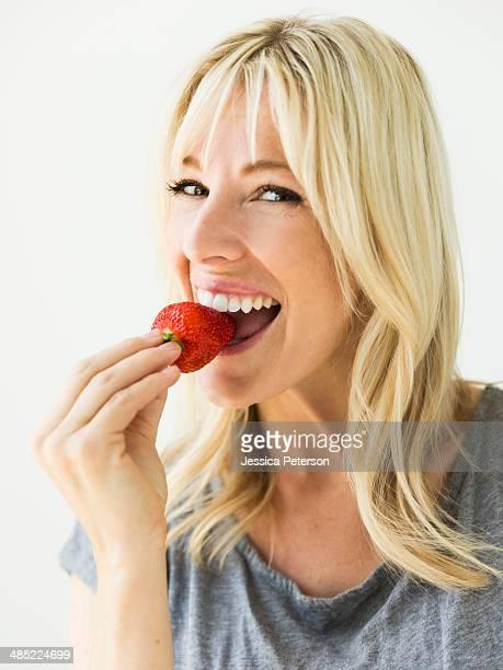 Woman eating fresh strawberry