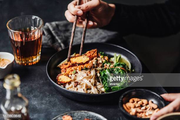 woman eating freshly made asian vegan meal - gourmet stock pictures, royalty-free photos & images
