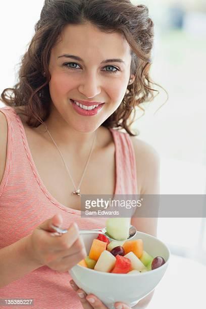 Woman eating fruit salad