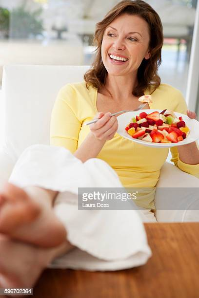 woman eating fruit salad - mid adult women stock pictures, royalty-free photos & images