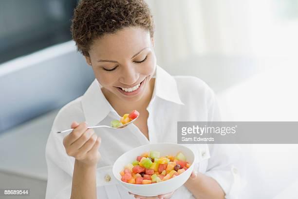 フルーツサラダを食べる女性