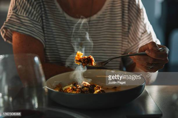 woman eating fusilli pasta with bolognese sauce - food stock pictures, royalty-free photos & images