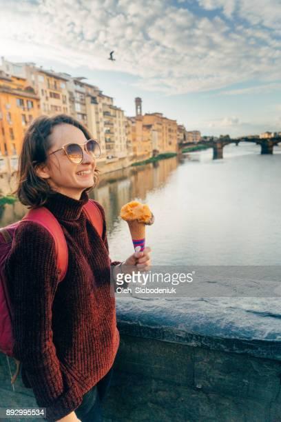 woman eating gelato on ponte veccio - ponte vecchio stock photos and pictures