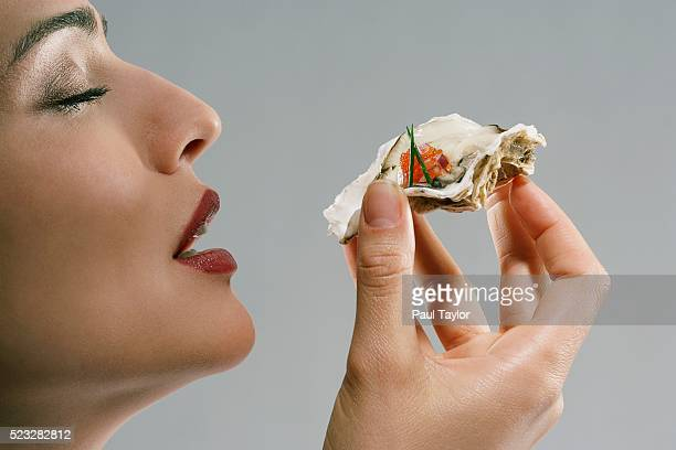 Woman eating gourmet oyster in shell