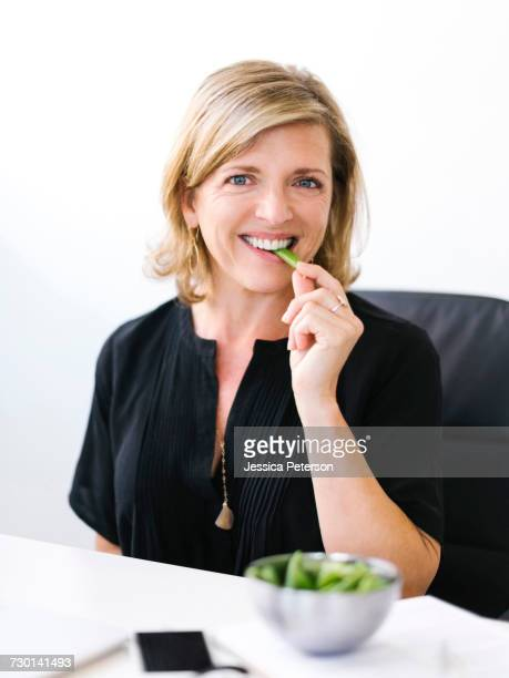 Woman eating green peas