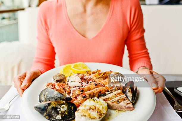 woman eating grilled seafood in a restaurant - seafood stock pictures, royalty-free photos & images