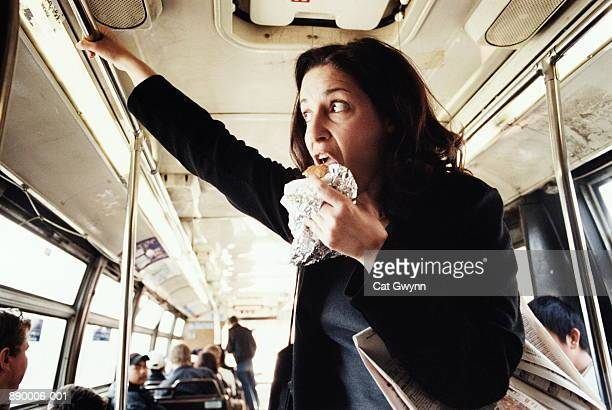 woman eating hamburger on bus - woman hurry stockfoto's en -beelden