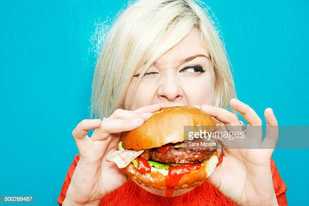 woman eating hamburger - hamburger stock pictures, royalty-free photos & images