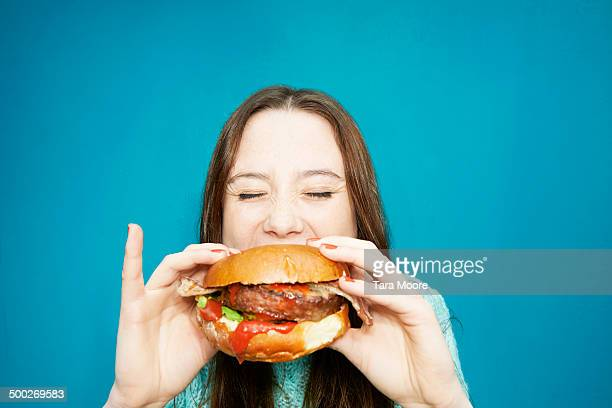 woman eating hamburger - burger stock pictures, royalty-free photos & images