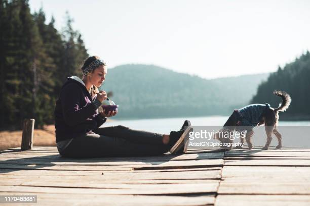 woman eating healthy food outdoor. - oatmeal stock pictures, royalty-free photos & images