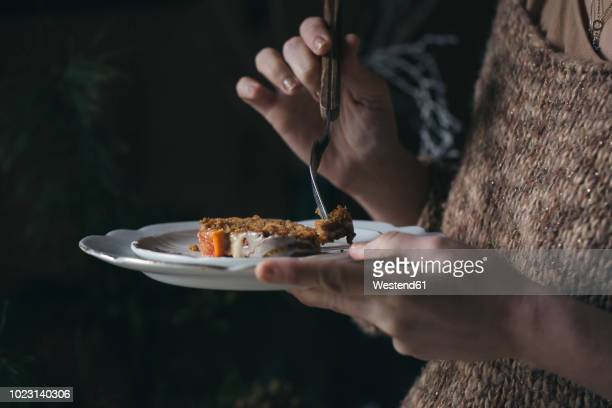 Woman eating home-baked Christmas cake, partial view